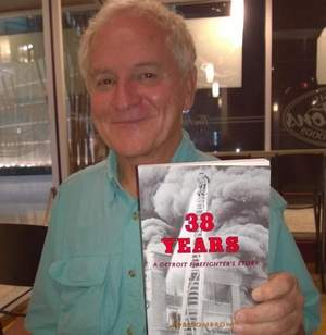 """Detroit Fire Cheif Bob Dombrowski shows off a copy of his new book """"38 Years - A Detroit Firefighter's Story"""""""